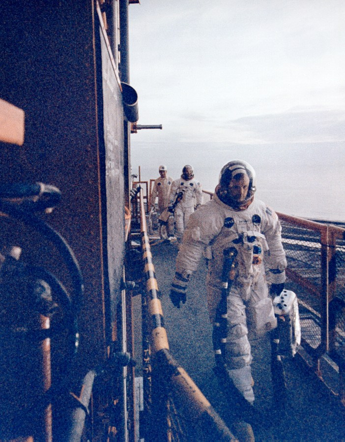 Neil Armstrong leads his crew across Swing Arm 9 carrying his oxygen supply